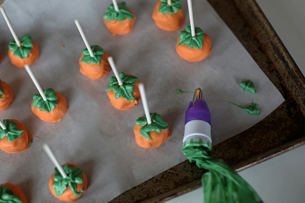Cookie dough pops with Butterfinger mixed in and decorated like mini pumpkins!
