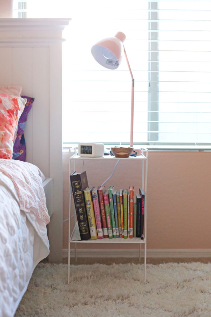 A light pink little girl's room with gold, wood, and coral accents